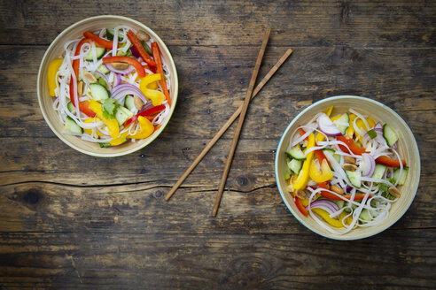 Two bowls of glass noodle salad with vegetables on dark wood - LVF05621