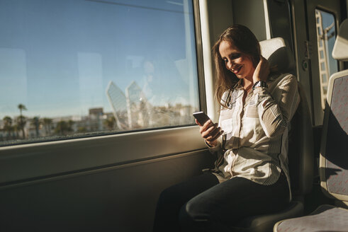 Smiling woman on a train looking at cell phone - KIJF00865