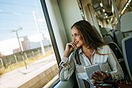 Smiling woman on a train using a tablet - KIJF00868