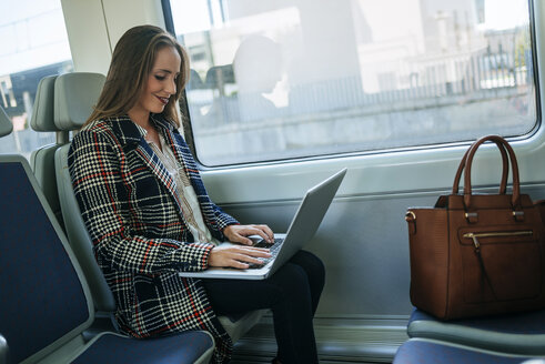 Businesswoman on a train using a laptop - KIJF00877