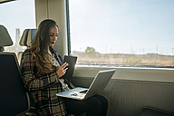 Businesswoman on a train with notebook and laptop - KIJF00880