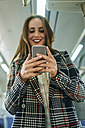 Smiling woman on a train looking at cell phone - KIJF00883