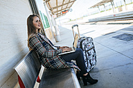 Businesswoman sitting on a bench at train station using a laptop - KIJF00895