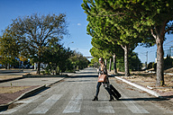 Woman with suitcase crossing street - KIJF00901