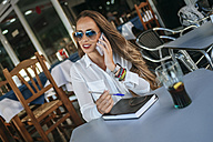 Woman talking on phone at a street cafe - KIJF00907
