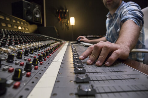Hand of a man working in the control room of a recording studio - ABZF01528