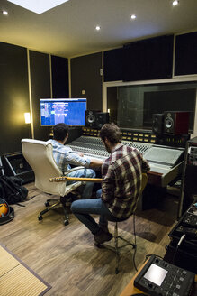 Guitar player and audio engineer in a recording studio - ABZF01534
