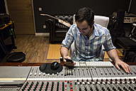 Man in the control room of a recording studio looking at cell phone - ABZF01537