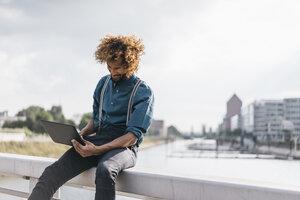 Young man using laptop outdoors - JOSF00417