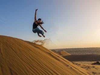 Oman, Al Raka, Young woman jumping from dune in Rimal Al Wahiba desert - AMF05082