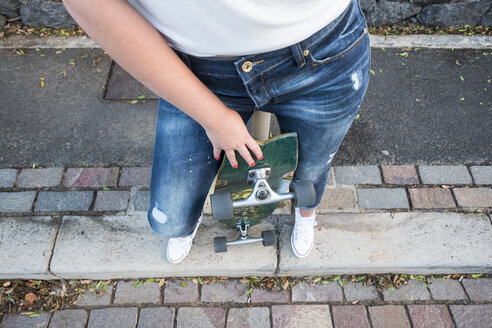 Young woman holding skateboard, partial view - SIPF01110