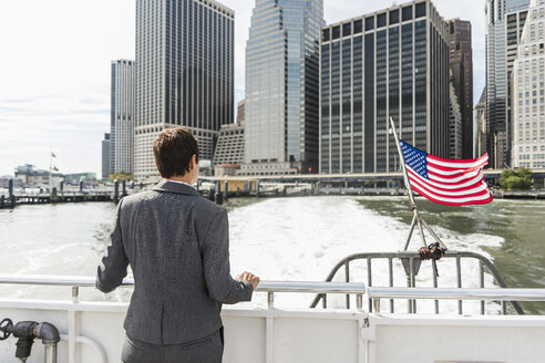 USA, Brooklyn, back view of businesswoman on a boat looking at Manhattan - UUF09247