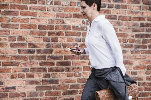 Businesswoman with briefcase and cell phone running in front of brick wall - UUF09256