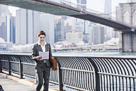 USA, Brooklyn, businesswoman reading papers in front of Manhattan skyscrapers - UUF09259