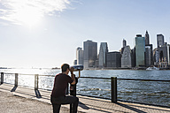 USA, Brooklyn, woman looking at Manhattan skyline with coin operated binoculars - UUF09271