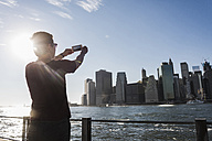 USA, Brooklyn, back view of woman  taking picture of Manhattan skyline with cell phone - UUF09274
