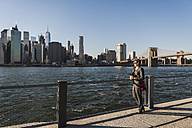 USA, Brooklyn, businesswoman with headphones looking at Manhattan skyline - UUF09277