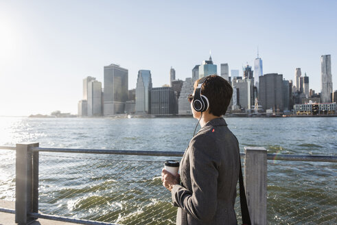 USA, Brooklyn, businesswoman with headphons and coffee to go in front of Manhattan skyline - UUF09280