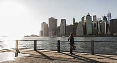 USA, Brooklyn, back view of businessman with briefcase looking at Manhattan skyline - UUF09283