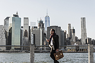 USA, Brooklyn, businessman with briefcase standing in front of Manhattan skyline - UUF09286