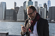 USA, Brooklyn, smiling businessman with earphones looking at his smartphone - UUF09289