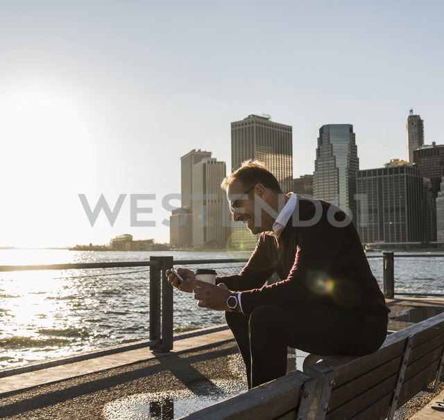 USA, Brooklyn, smiling man with coffee to go sitting on bench looking at smartphone - UUF09295