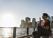 USA, Brooklyn, woman with coffee to go sitting on bench looking at view - UUF09298