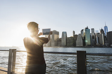USA, Brooklyn, back view of woman taking picture of Manhattan skyline with tablet - UUF09301