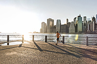 USA, Brooklyn, man jogging in front of Manhattan skyline in the evening - UUF09304