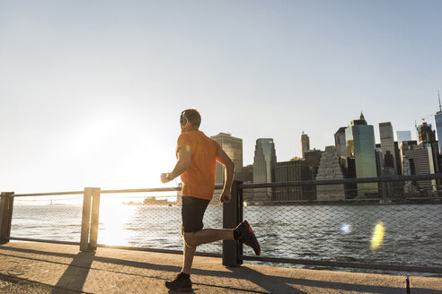 USA, Brooklyn, man jogging in front of Manhattan skyline in the evening - UUF09307