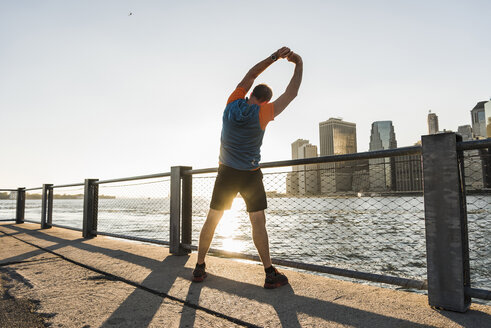 USA, Brooklyn, back view of man doing stretching exercises in the evening - UUF09310