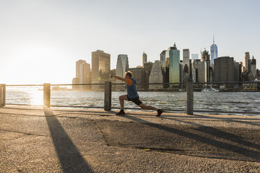 USA, Brooklyn, man doing stretching exercises in front of Manhattan skyline in the evening - UUF09313