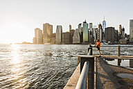 USA, Brooklyn, man doing stretching exercises in front of Manhattan skyline in the evening - UUF09316