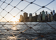 USA, Brooklyn, view to Manhattan through fence at twilight - UUF09319