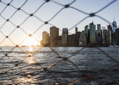 USA, Brooklyn, view to Manhattan through fence at twilight - UUF09319