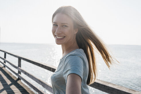 Portrait of happy young woman on jetty at backlight - KNSF00667
