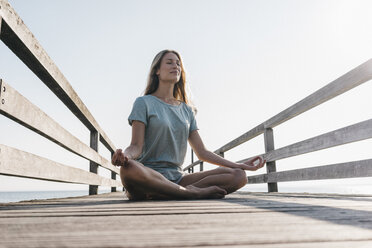 Young woman practising yoga on jetty - KNSF00670