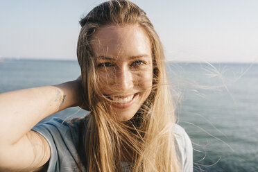 Portrait of happy young woman with blowing hair in front of the sea - KNSF00673