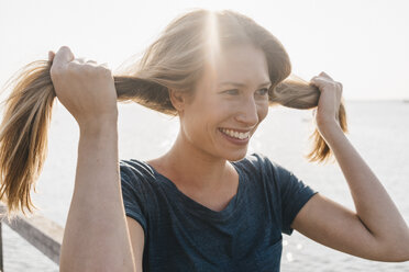 Portrait of smiling young woman with hand in her hair on jetty - KNSF00679