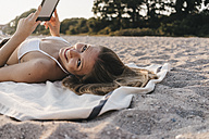 Smiling young woman lying on blanket on the beach with tablet - KNSF00688