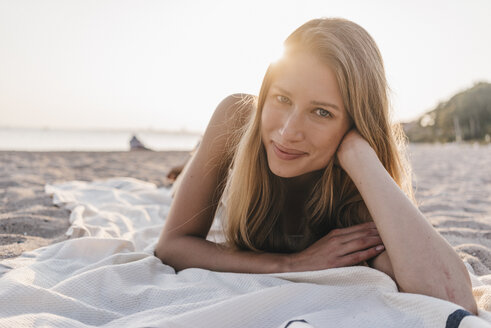 Portrait of young woman lying on blanket on the beach - KNSF00691