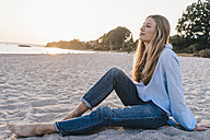 Young woman relaxing on the beach in the evening - KNSF00697