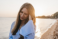 smiling young woman on the beach at sunset - KNSF00700