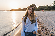 Smiling young woman on the beach at twilight - KNSF00703