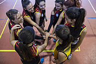 Female volleyball team huddling and stacking hands - ABZF01565