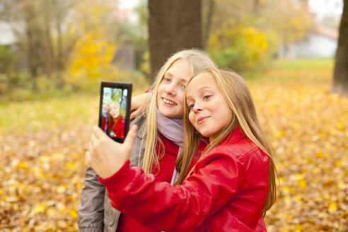 Two happy girls taking selfie with cell phone in autumn - MAEF12058