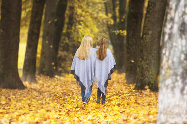 Back view of two girls sharing cape in autumn - MAEF12061