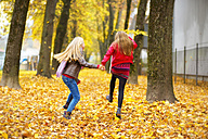 Back view of two jumping girls in autumn - MAEF12064