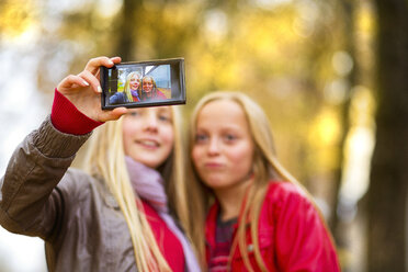 Two girls taking selfie with cell phone in autumn - MAEF12067