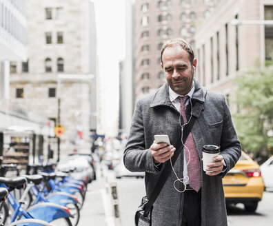 USA, New York City, businessman on the move in Manhattan looking on cell phone - UUF09324